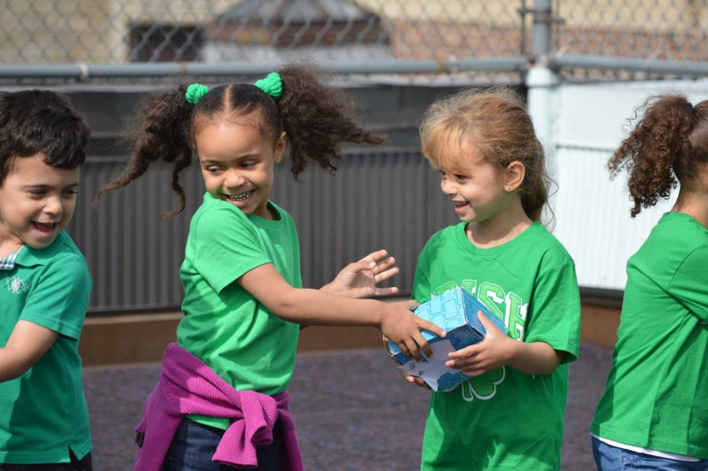 Kids pass parcels between each other to practice teamwork at a Play At The Core event. © PATC