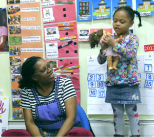 A play leader helps a young girl through play therapy