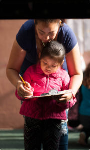 Our Impact photo header showing a volunteer leading a girl through writing exercises